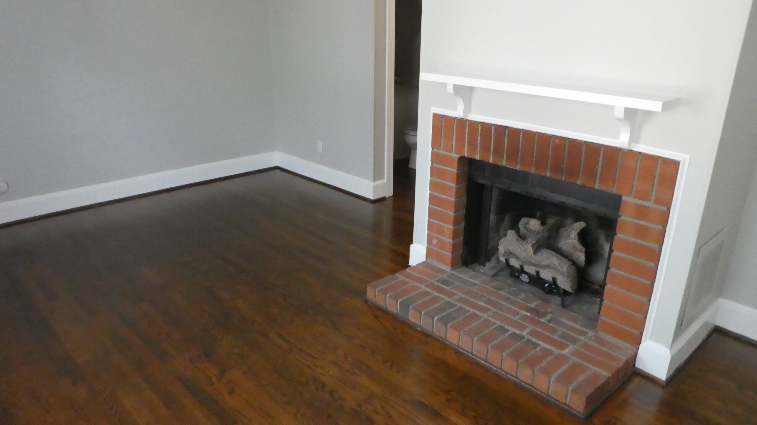 Photo of the living room at Wilmington Square with fireplace and dark oak floors