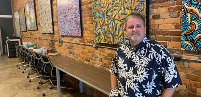 The artist stands before his work in the Century 21 office