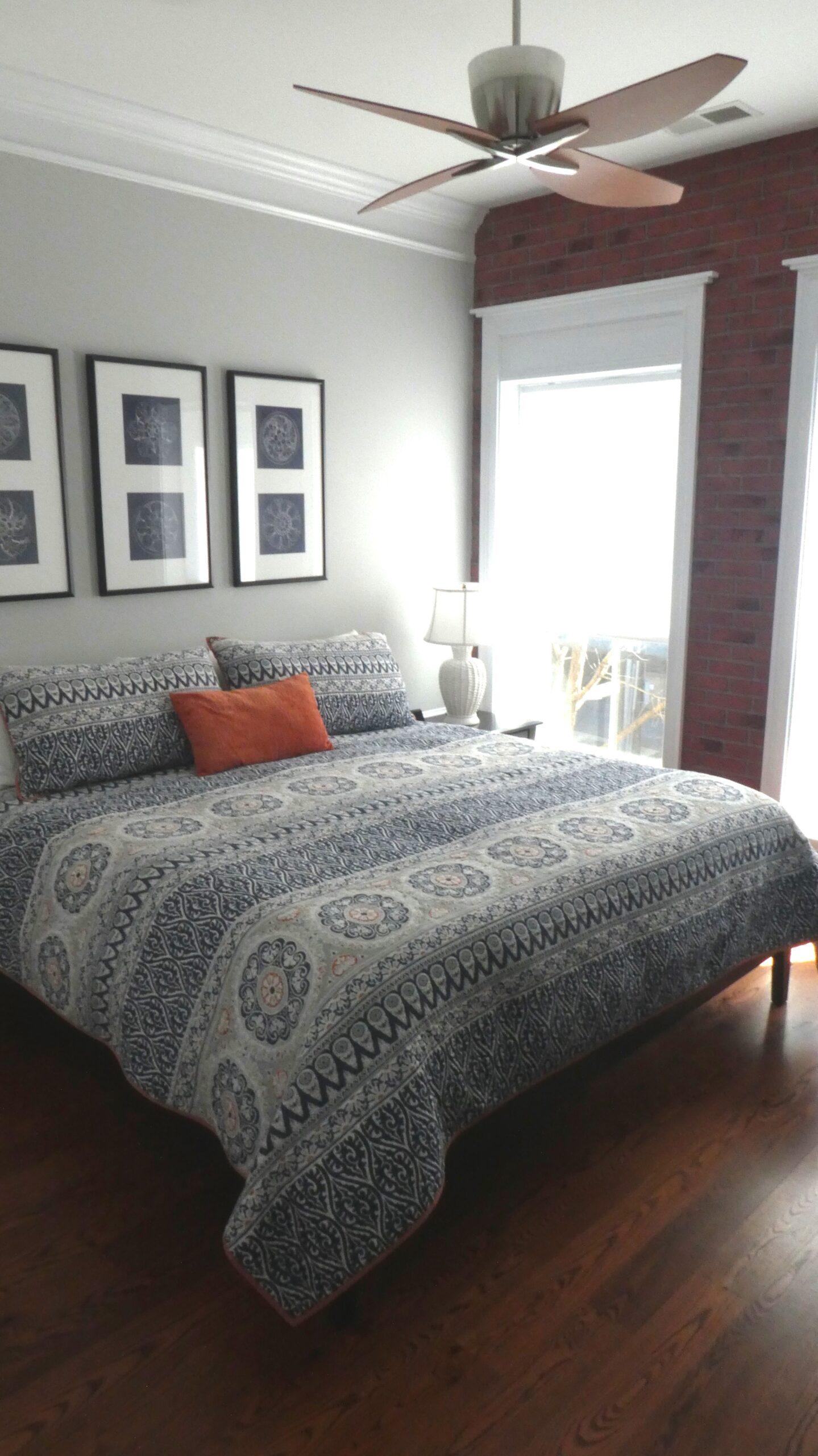 Bedroom with oversized windows, exposed brick wall and dark oak floors
