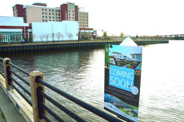 'Coming Soon' sign next to the Riverwalk showing the future location of The Strands houseboat community